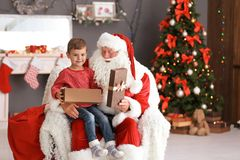 Le garçon mignon avec le boîte-cadeau se reposant sur le ` authentique de Santa Claus enroulent à l'intérieur image stock