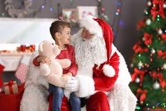Le garçon mignon avec l'ours de nounours se reposant sur le ` authentique de Santa Claus enroulent à l'intérieur images libres de droits