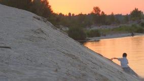 Le garçon mignon court et saute d'une colline de sable au coucher du soleil Reste actif de l'enfant banque de vidéos