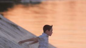 Le garçon mignon court et saute d'une colline de sable au coucher du soleil Reste actif de l'enfant clips vidéos