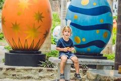 Le garçon mignon de petit enfant avec des oreilles de lapin ayant l'amusement avec les oeufs de pâques traditionnels chassent, de Image stock