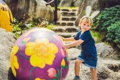 Le garçon mignon de petit enfant avec des oreilles de lapin ayant l'amusement avec les oeufs de pâques traditionnels chassent, de Photo libre de droits