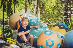 Le garçon mignon de petit enfant avec des oreilles de lapin ayant l'amusement avec les oeufs de pâques traditionnels chassent, de Image libre de droits