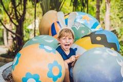 Le garçon mignon de petit enfant avec des oreilles de lapin ayant l'amusement avec les oeufs de pâques traditionnels chassent, de Photographie stock