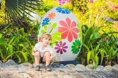 Le garçon mignon de petit enfant avec des oreilles de lapin ayant l'amusement avec les oeufs de pâques traditionnels chassent, de Images stock