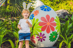 Le garçon mignon de petit enfant avec des oreilles de lapin ayant l'amusement avec les oeufs de pâques traditionnels chassent, de Images libres de droits