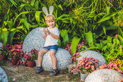 Le garçon mignon de petit enfant avec des oreilles de lapin ayant l'amusement avec les oeufs de pâques traditionnels chassent, de Photographie stock libre de droits