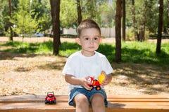 Le garçon mignon de petit enfant joue avec la voiture de jouet en parc sur la nature à l'été Photographie stock