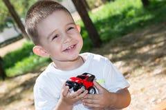 Le garçon mignon de petit enfant joue avec la voiture de jouet en parc sur la nature à l'été Photos stock