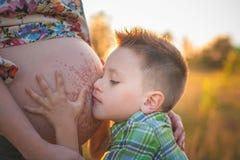 Le garçon mignon embrassant le sien enfante le ventre enceinte Image libre de droits