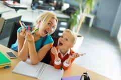 Le garçon mignon et sa maman s'asseyent au bureau dans les crayons de bureau et de prise Photos libres de droits
