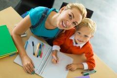 Le garçon mignon et sa maman s'asseyent au bureau dans les crayons de bureau et de prise Image libre de droits