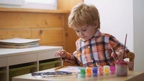 Le garçon mignon heureux colore ses mains Faire la peinture de doigt Thérapie d'art pour des enfants Psychologie de la personnali banque de vidéos