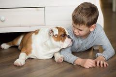 Le garçon mignon joue sur le plancher sur un tapis avec des chiots de bouledogue anglais Photo stock