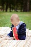Le garçon mignon mange la pastèque mûre photo libre de droits