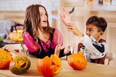 Le garçon mignon portant l'électrodéposition squelettique de costume de Halloween dupe avec une soeur plus âgée image stock