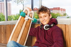 Le garçon mignon positif tient la planche à roulettes tout en se reposant Images stock
