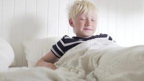 Le garçon mignon se réveille le matin dans un lit blanc et en sirotant banque de vidéos