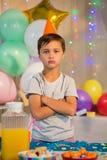 Le garçon mignon se tenant avec des bras a croisé à la fête d'anniversaire images stock