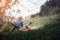Le garçon mignon se trouve sur l'herbe avec une guitare sur le coucher du soleil Photographie stock