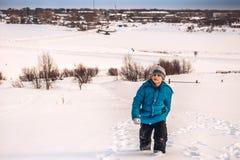 Le garçon monte les banques couvertes de neige de la rivière Image libre de droits