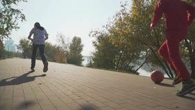 Le garçon monte un scooter L'enfant court en parc donnant un coup de pied la boule rouge banque de vidéos