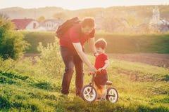 Le garçon monte un vélo d'équilibre dans la campagne Photo stock