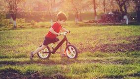 Le garçon monte un vélo d'équilibre dans la campagne image libre de droits