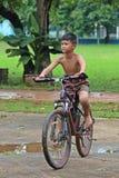 Le garçon monte une bicyclette sur la route photo libre de droits