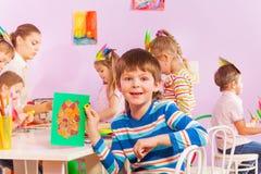 Le garçon montre le sien ouvré avec le papier dans la classe Images libres de droits
