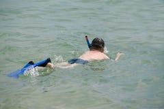 Le garçon nage avec un masque et un tube Photo stock