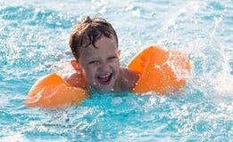 Le garçon nage dans la piscine Photographie stock libre de droits