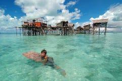 Le garçon nage par la maison sur des stlits Photo libre de droits