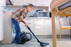 Le garçon nettoie à l'aspirateur le plancher de cuisine Il range les flocons d'avoine dispersés sur la tuile grise Vue de côté photographie stock libre de droits
