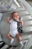 Le garçon nouveau-né se situe dans un lit rond Photographie stock