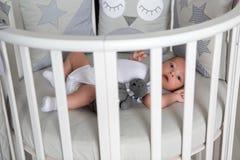Le garçon nouveau-né se situe dans un lit rond Photographie stock libre de droits