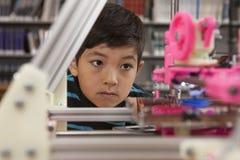 Le garçon observe l'imprimante dans l'action photographie stock