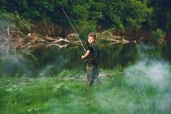 Le garçon pêche des poissons en rivière avec une canne à pêche Photographie stock libre de droits
