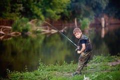 Le garçon pêche des poissons en rivière avec une canne à pêche Image libre de droits