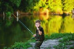 Le garçon pêche des poissons en rivière avec une canne à pêche Images stock