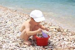 Le garçon par la mer joue le cuisinier. Image libre de droits