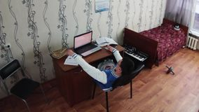 Le garçon paresseux s'asseyent de retour sur la chaise au carnet dans la chambre de dortoir Lit avec la couverture rouge étudiant banque de vidéos