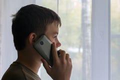 Le garçon parle au téléphone et regarde la fenêtre photos libres de droits