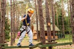 Le garçon passe par des obstacles sur une ville de corde photos stock