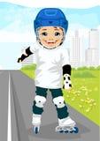Le garçon patinant dessus fait du roller sur le trottoir le long de la route Image stock