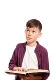 Le garçon a pensé avec un livre dans des ses mains Image libre de droits
