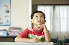 Le garçon pensant dans la salle de classe Image stock
