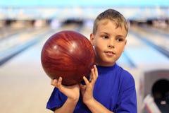 Le garçon pensant retient la bille dans le bowling Photographie stock libre de droits