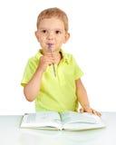 Le garçon pense avec le stylo dans la bouche photo stock