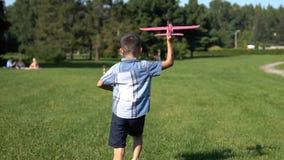 Le garçon pilote lance un avion de jouet en parc Mouvement lent banque de vidéos
